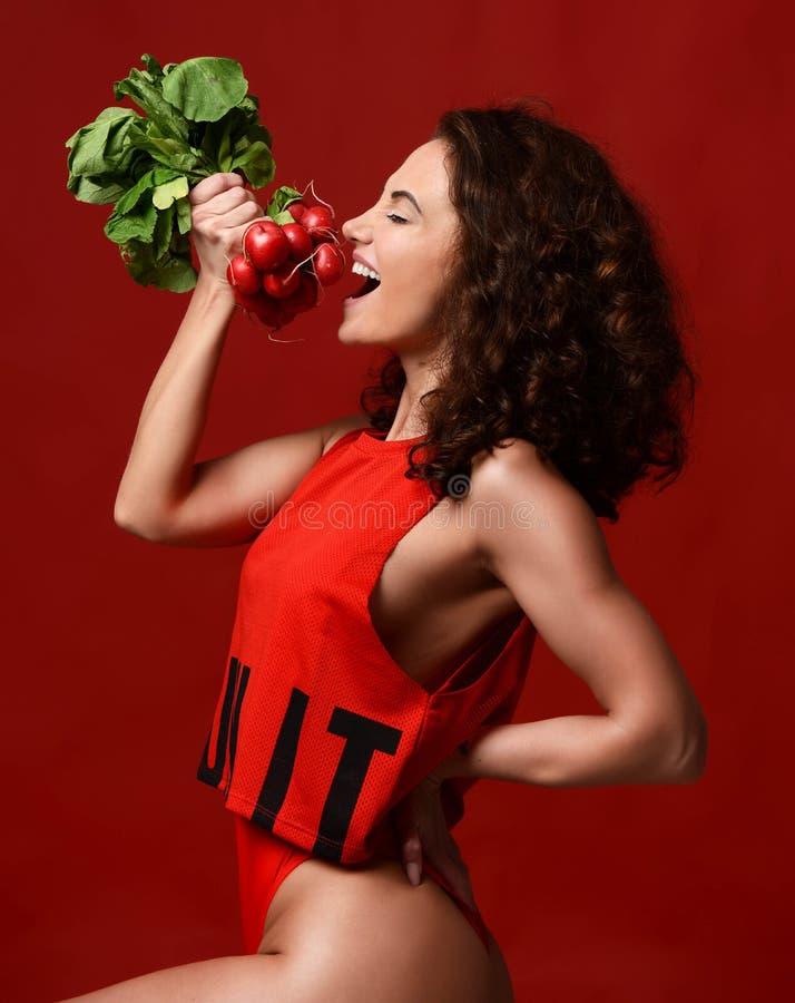 La jeune femme assez gaie de sport posant avec le vert frais de radis part photographie stock