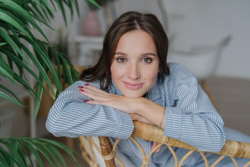 La jeune femme attirante avec les cheveux foncés, intéressants composent des regards directement à l'appareil-photo, se penche de images libres de droits