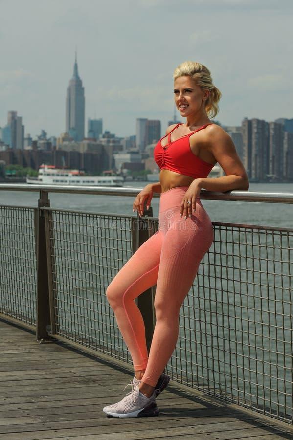 La jeune femme attirante d'ajustement s'est habillée dans les vêtements de sport lumineux posant dehors image libre de droits