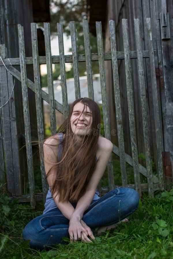 La jeune femme attirante dans des jeans s'assied près d'une barrière en bois images stock