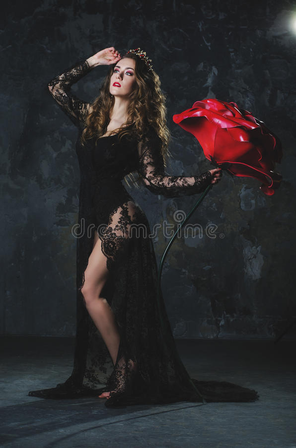 La jeune femme attirante dans une longue robe noire avec très un grand s'est levée sur un fond grunge de mur images stock