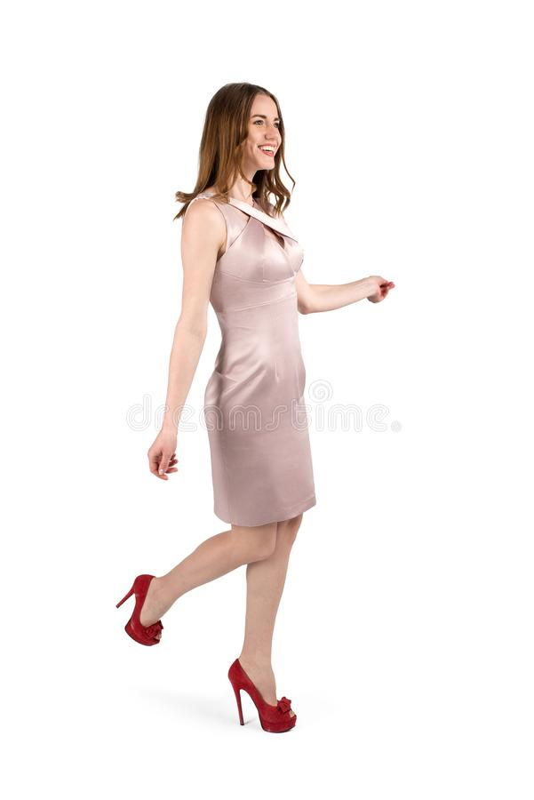La jeune femme attirante dans une robe de soirée va sur une partie photo libre de droits
