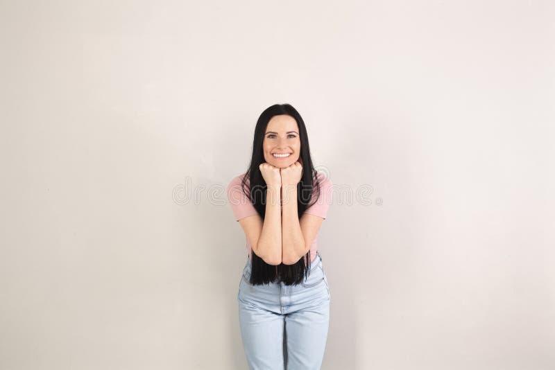 La jeune femme attirante de brune avec de longs cheveux se tient prêt le fond gris est recourbement de sourire en avant Son visag image stock
