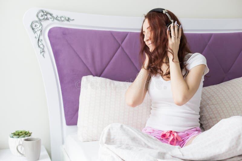 La jeune femme attirante de brune s'assied pendant le matin dans son lit avec des ?couteurs et un smartphone et ?coute la musique photo libre de droits