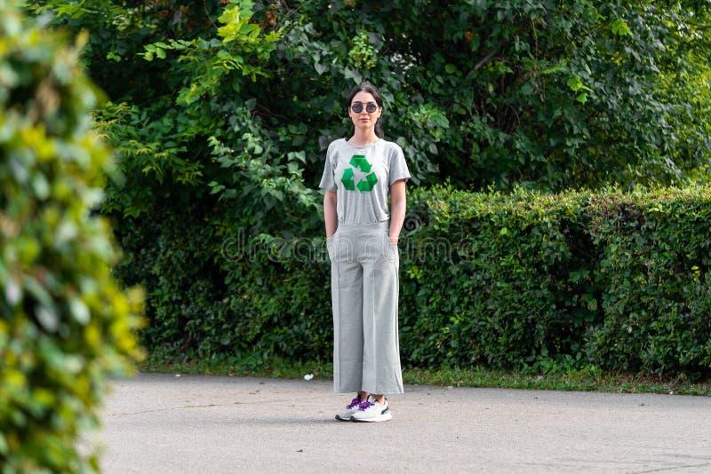La jeune femme attirante de sourire dans le T-shirt gris avec réutilisent le symbole en parc photo stock