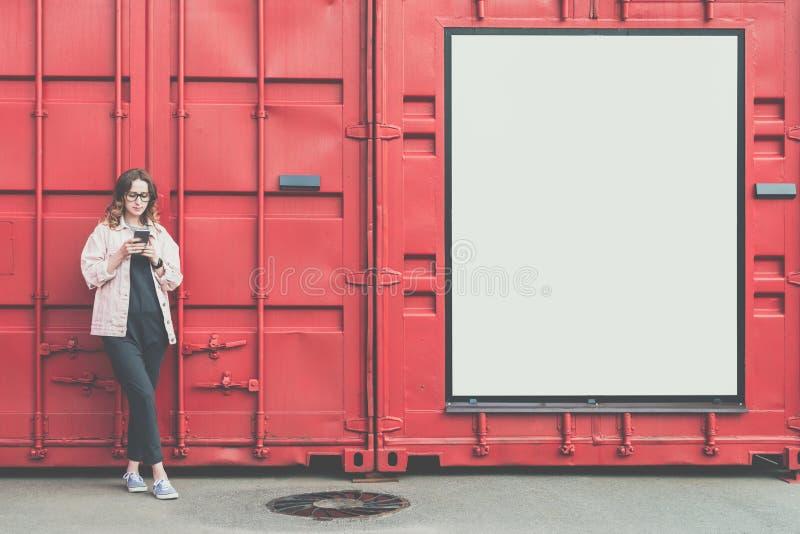 La jeune femme attirante en verres se tient dehors sur le fond rouge de mur en métal, regardant l'écran du téléphone, smartphone  photographie stock