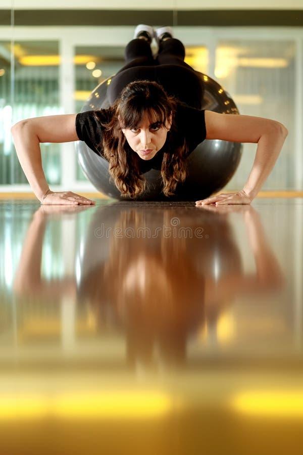 La jeune femme attirante fait des exercices se trouvant sur la boule gymnastique, pilates photographie stock