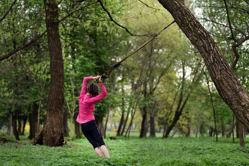 La jeune femme attirante fait le corps s'étendant avec le streptocoque de forme physique de trx image stock