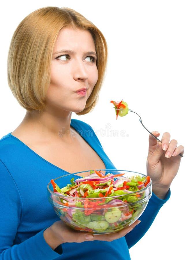 La jeune femme attirante mange de la salade utilisant la fourchette photographie stock