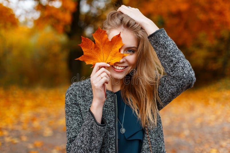 La jeune femme attirante mignonne heureuse avec un sourire dans un manteau à la mode se tient en parc et couvre son visage photos libres de droits