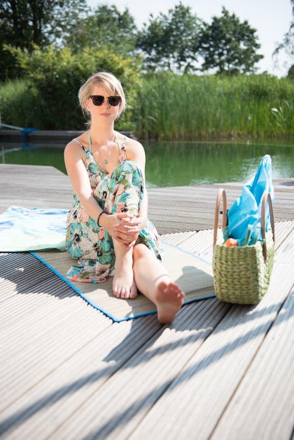 La jeune femme attirante s'assied à la piscine images libres de droits