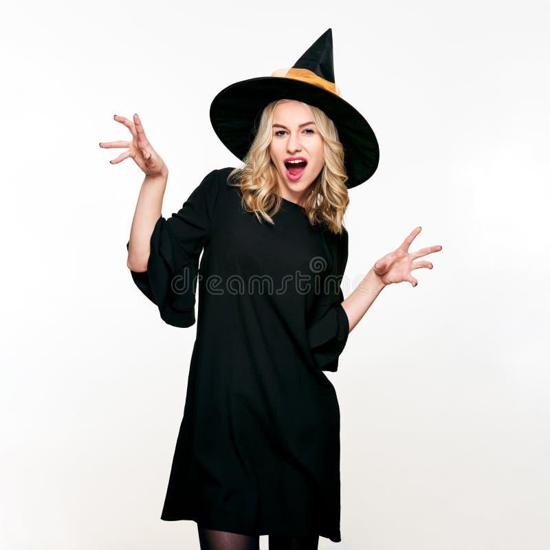 La jeune femme attirante s'est habillée dans le costume de Halloween de sorcière d'isolement au-dessus du fond blanc Sorcière sen image libre de droits