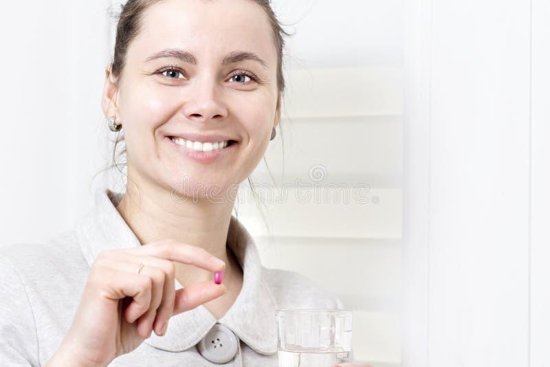 La jeune femme attirante se tient en sa pilule de main et verre de propre image libre de droits