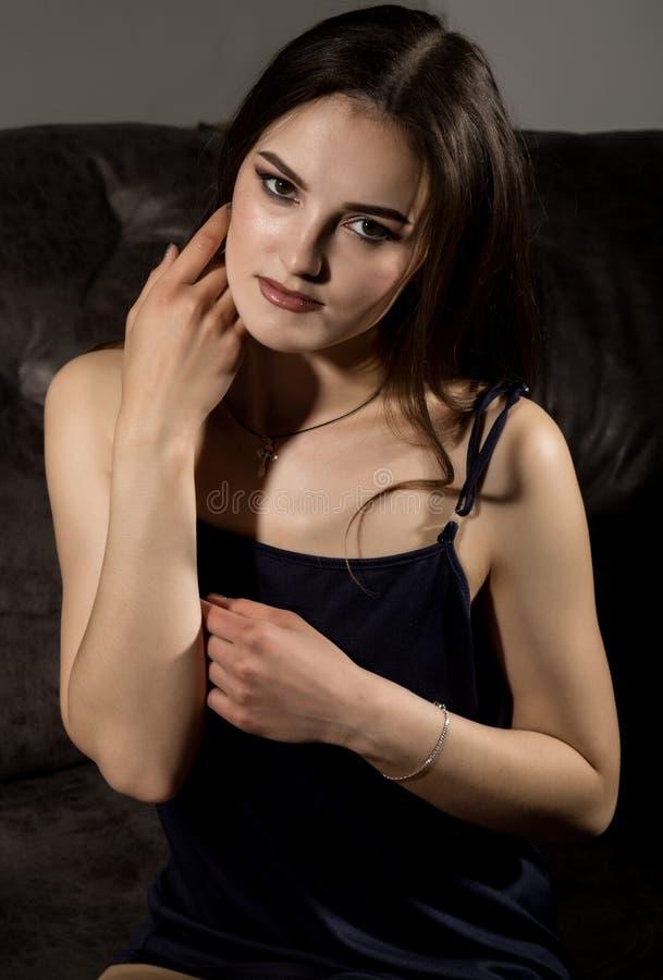 La jeune femme attirante sensuelle dans les pyjamas en soie pose sur un sofa image stock