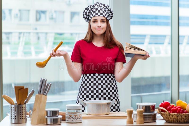La jeune femme au foyer se référant au livre de recette photographie stock