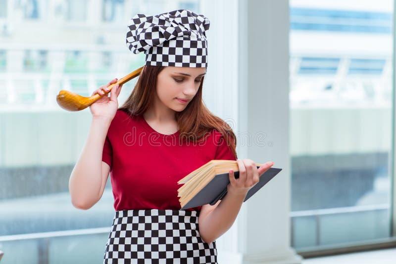 La jeune femme au foyer se référant au livre de recette photos stock