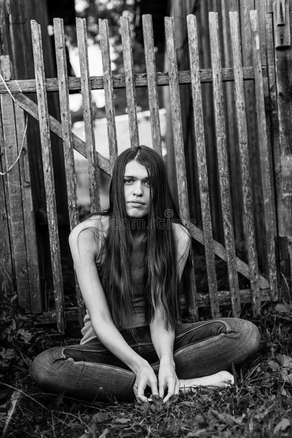 La jeune femme aux cheveux longs attirante dans des jeans s'assied près d'une barrière en bois image libre de droits