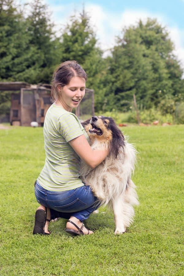 La jeune femme avec des colleys poursuivent jouer sur une herbe image stock