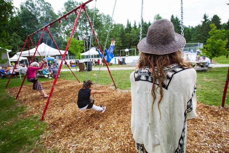 La jeune femme avec des dreadlocks s'assied dans l'oscillation d'un enfant au parc photo libre de droits
