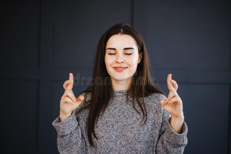La jeune femme avec des yeux a fermé les doigts croisés photo stock