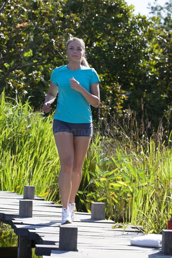 La jeune femme avec l'été court-circuite le fonctionnement en parc naturel dehors photo libre de droits