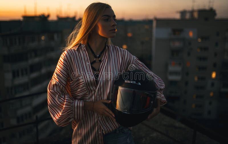 La jeune femme avec le casque de moto se tient contre du backg urbain photographie stock