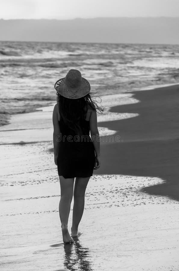 La jeune femme avec le chapeau marchant en plage au coucher du soleil Fond noir et blanc photos libres de droits