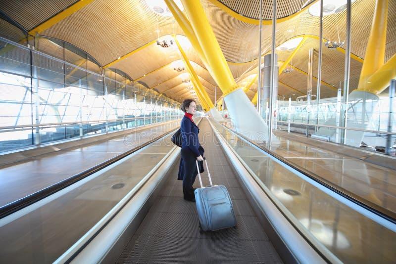 La jeune femme avec le grand sac de voyage se tient dans le couloir photographie stock