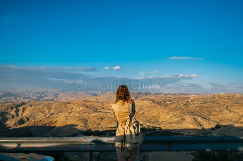 La jeune femme avec le sac à dos se tient en haut de la montagne photographie stock libre de droits