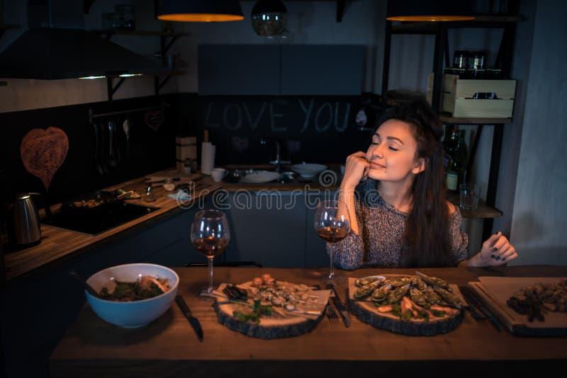 La jeune femme avec les yeux fermés s'assied à la table avec la nourriture et la victoire photos libres de droits