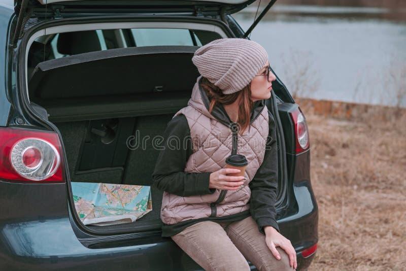 La jeune femme avec la tasse de café s'assied dans le tronc ouvert de la voiture près de la rivière et de la carte de route de ob photo stock