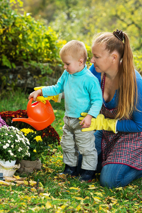 La jeune femme avec un enfant plantent des fleurs photos stock