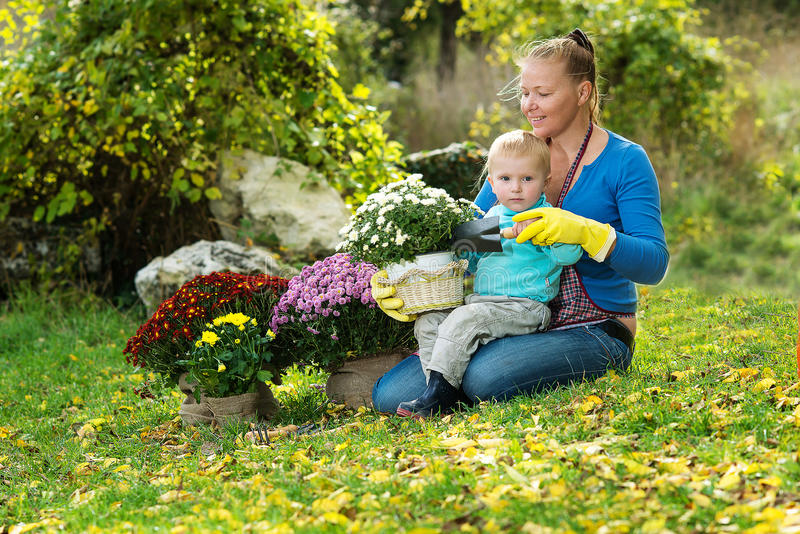 La jeune femme avec un enfant plantent des fleurs photo libre de droits