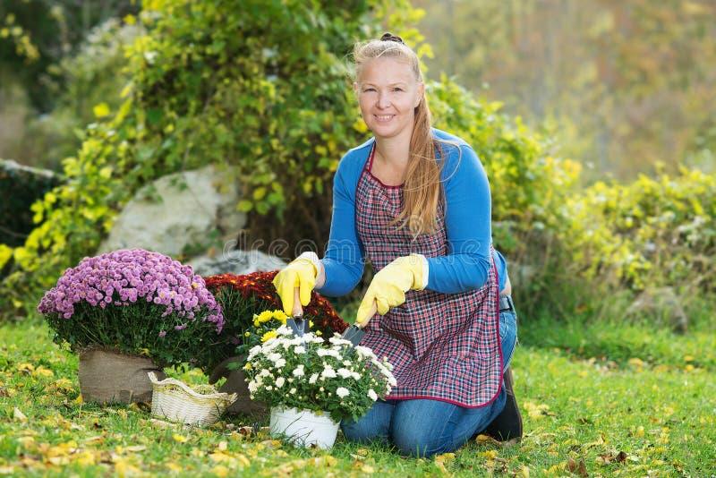 La jeune femme avec un enfant plantent des fleurs images libres de droits