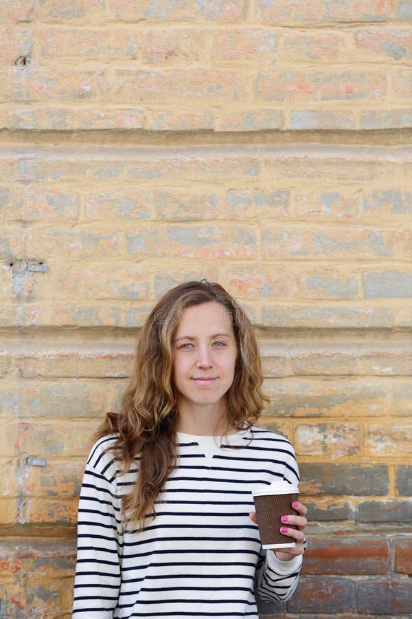 La jeune femme avec une tasse vont café sur le vieux mur de fond photographie stock libre de droits