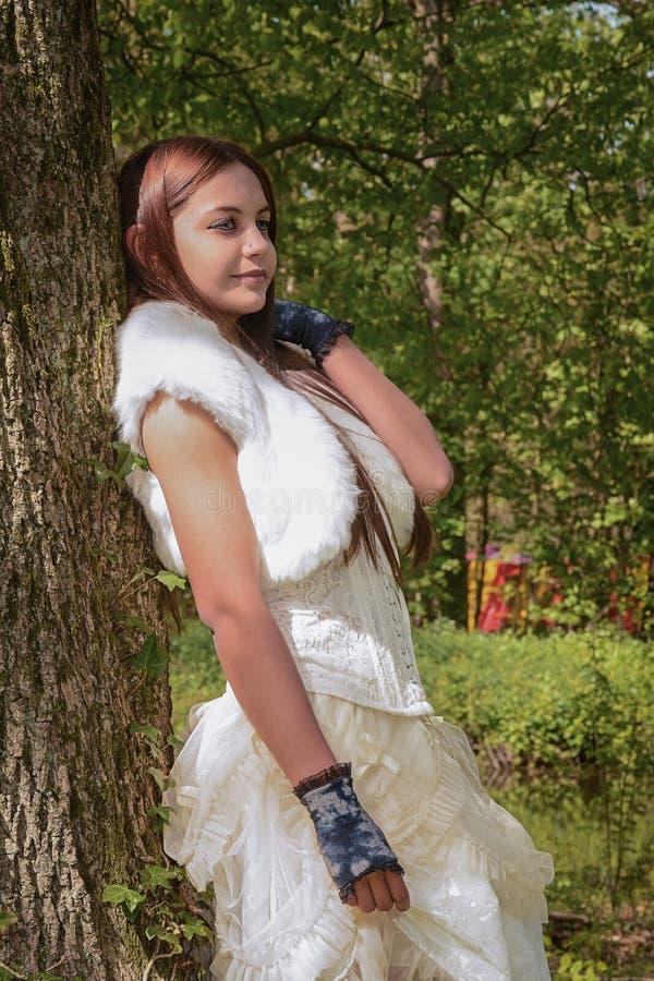 La jeune femme belle se penche avec elle de retour contre un arbre à photographie stock libre de droits