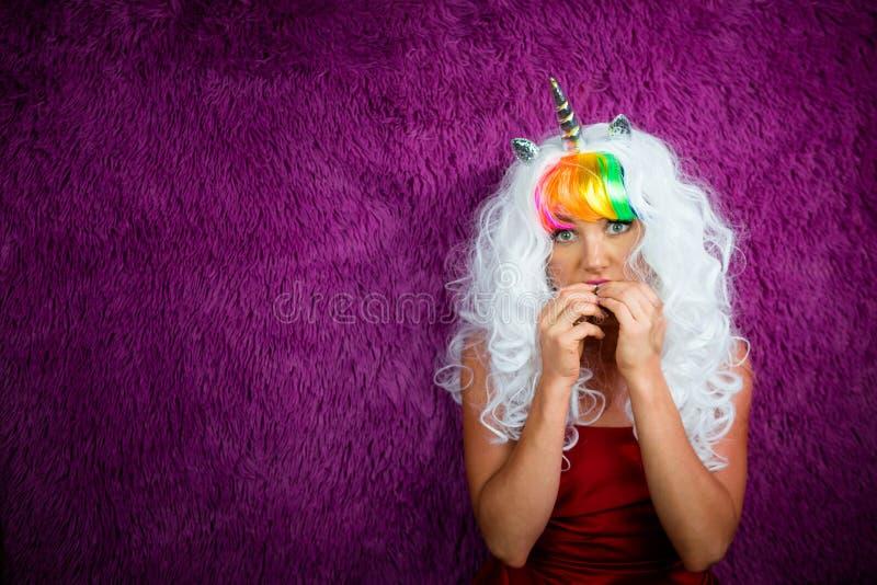 La jeune femme bizarre dans la perruque peu commune se tient sur le fond pourpre photographie stock libre de droits