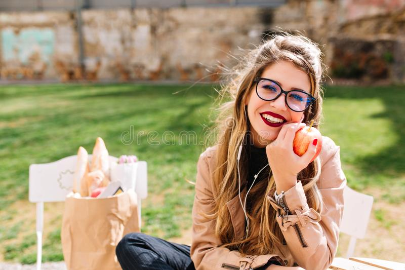 La jeune femme blanche mignonne avec la pomme rouge regarde à disposition rêveusement la caméra tout en se reposant en parc après photos libres de droits