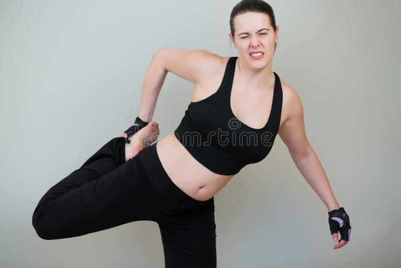 La jeune femme blanche sur une séance d'entraînement de forme physique fléchit la jambe et la douleur d'expériences photos libres de droits
