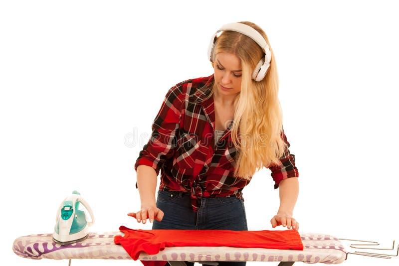 La jeune femme blonde écoute la musique et chante pendant qu'elle repasse photo stock