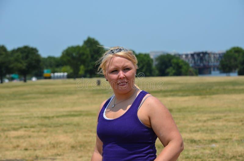 La jeune femme blonde adulte se tient en parc pendant l'été avec son tounge, la pensée, et la perspective, se concentrant dessus photographie stock libre de droits