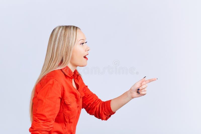 La jeune femme blonde, avec des émotions positives indique un gris de retour images stock