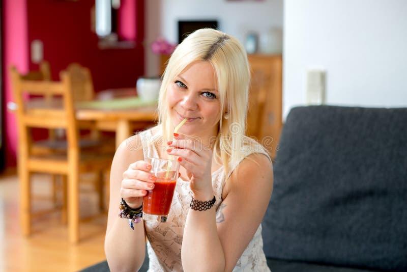 La jeune femme blonde boit du jus rouge photographie stock libre de droits