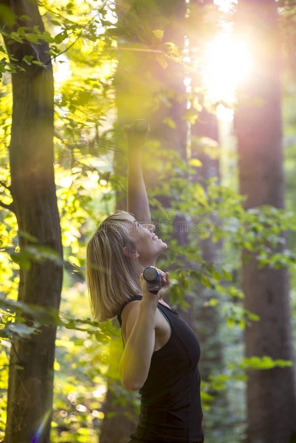 La jeune femme blonde heureuse faisant des pilates s'exercent dans une forêt à s image libre de droits