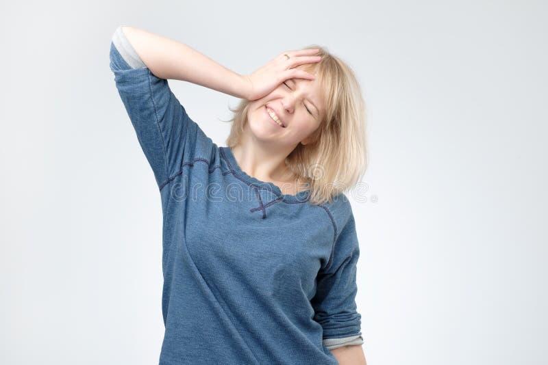 La jeune femme blonde portant le pulover bleu étonné avec la main sur la tête pour l'erreur, se rappellent l'erreur photo libre de droits