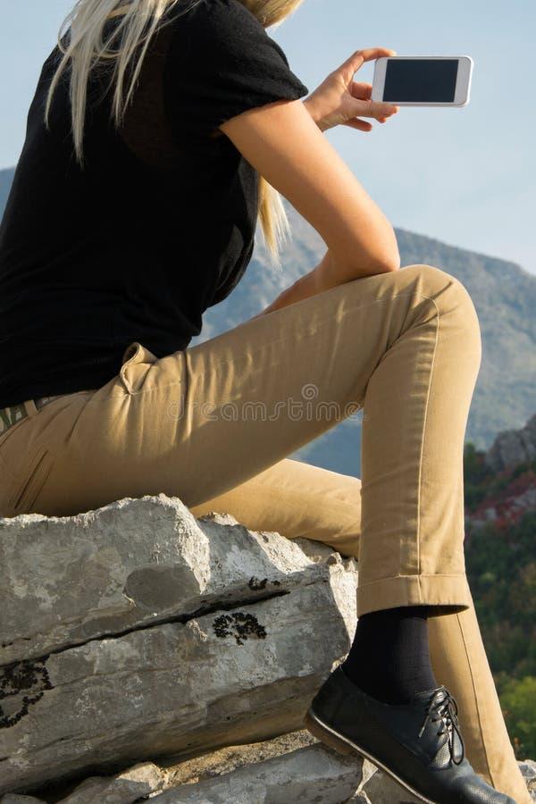 La jeune femme blonde s'asseyant au bord de la falaise de montagne prend la photo avec le smartphone sur la belle crête de montag images stock