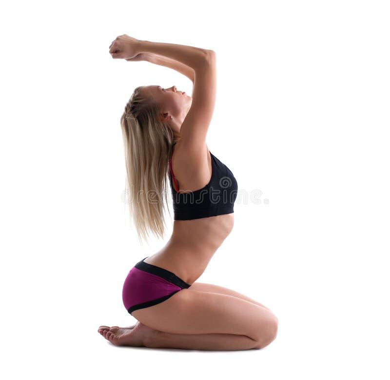 La jeune femme blonde s'asseyent dans la pose de youga d'isolement photographie stock