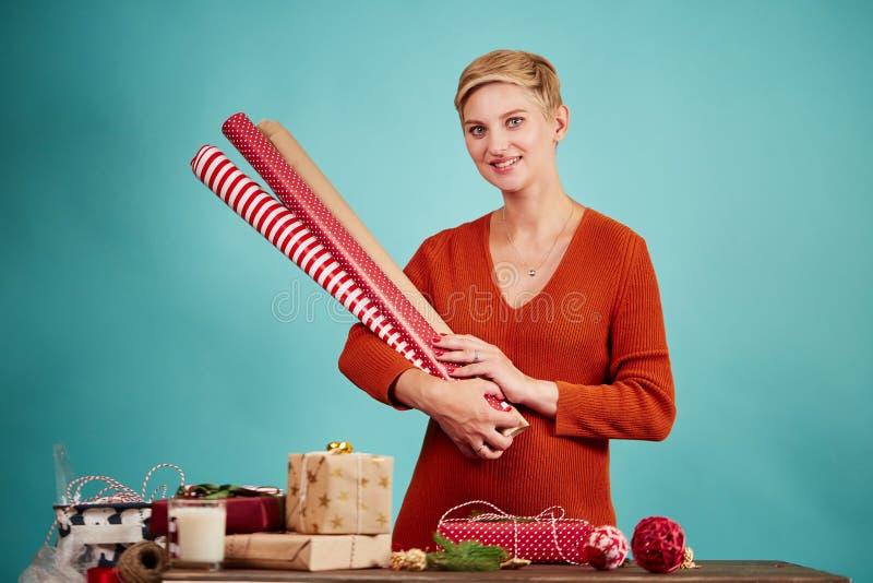 La jeune femme blonde se tenant en papier d'emballage de mains roule pour des cadeaux, d'isolement images libres de droits