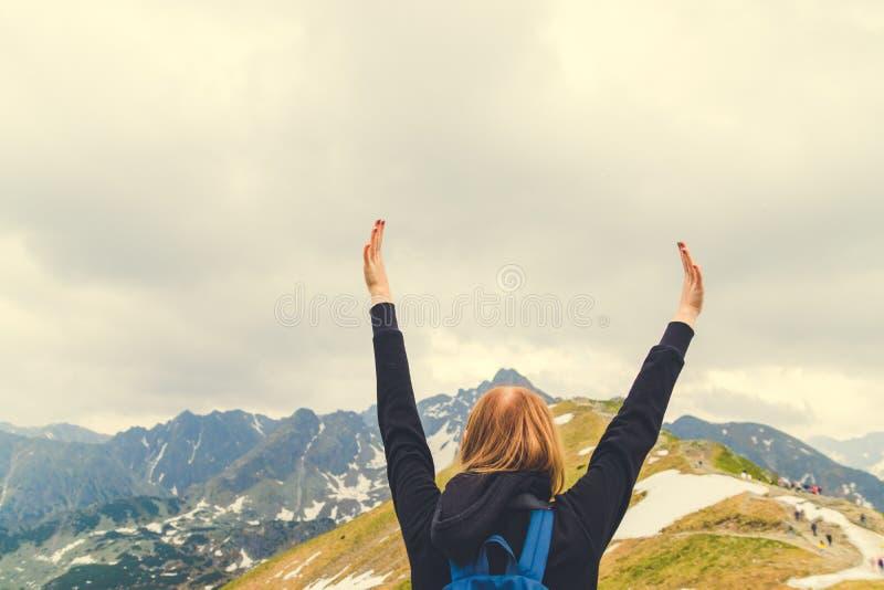 La jeune femme blonde se tient avec ses bras a augmenté, atteignant le dessus, admirant le paysage de montagne photos stock