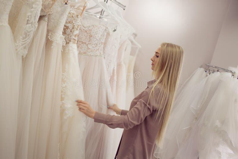 La jeune femme blonde semble la robe différente sur le cintre Boutique nuptiale image stock